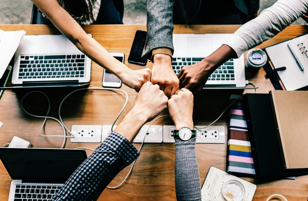 Five fists coming together in an office setting, symbolizing teamwork