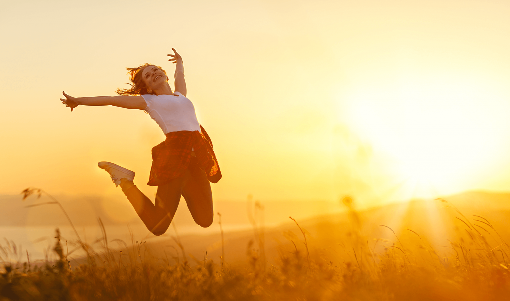 Woman jumping in front of sunset