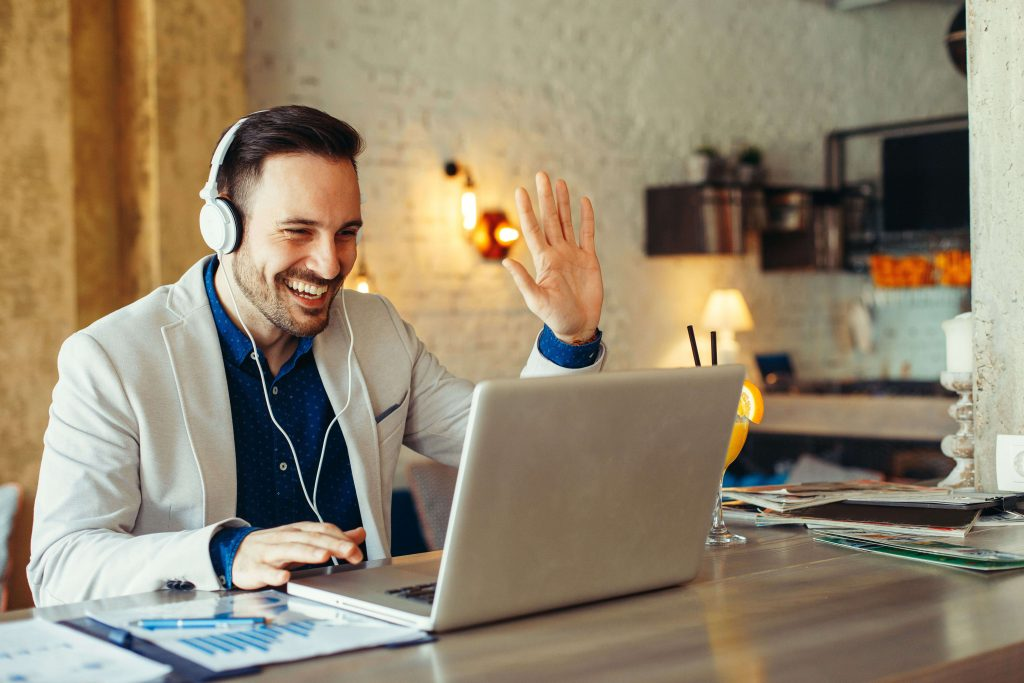 Smiling man uses remote working tools, including computer and headset, to do his work.