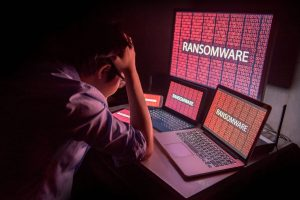 Young man holds head, showing he's upset by ransomware attack