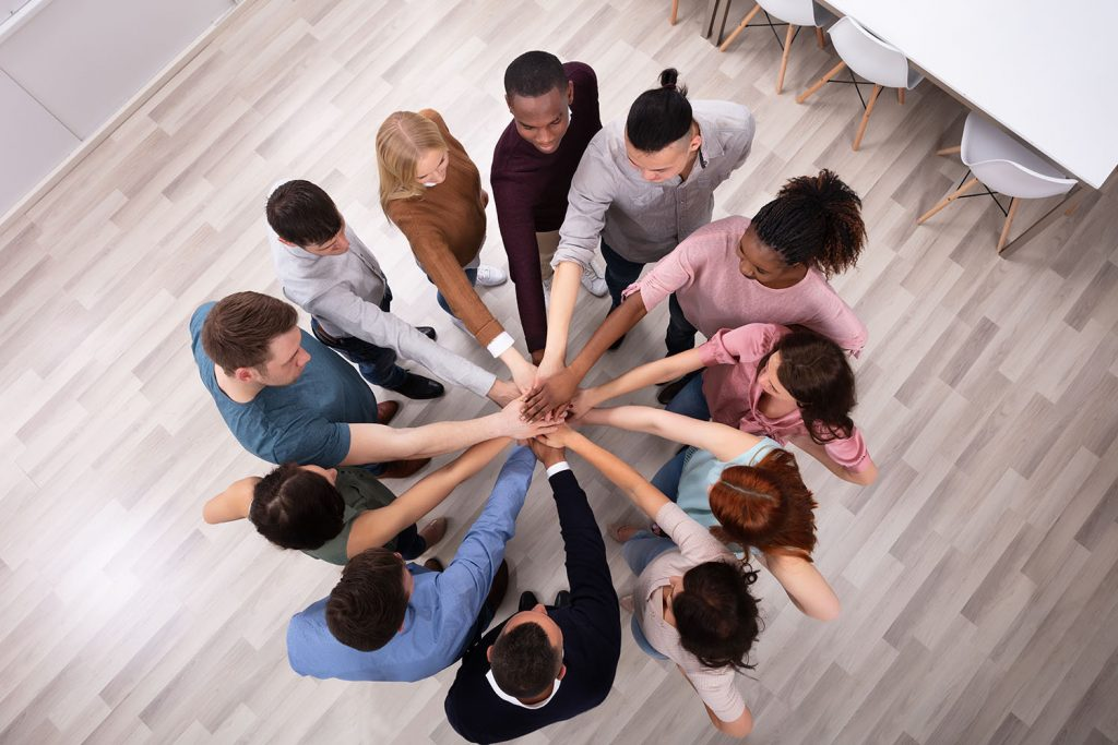 Teammates stack hands with each other to celebrate OpEx.
