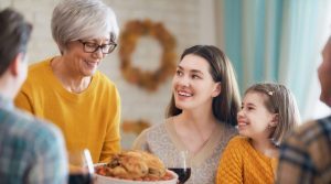 Family gathers around turkey at Thanksgiving