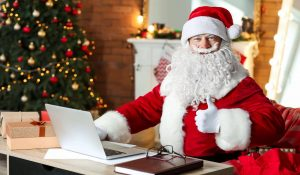 Santa's going over his nice and naughty cybersecurity lists. He sits at a laptop and gives a thumbs up to the camera. There's a Christmas tree behind him.