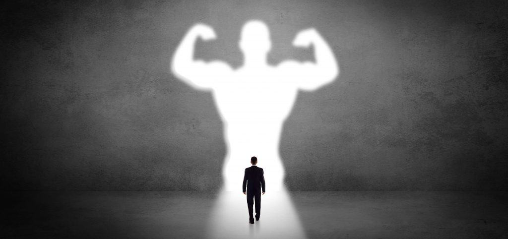 Image of businessman walking toward strong silhouette basked in light, showing he has strong IT goals for 2020.