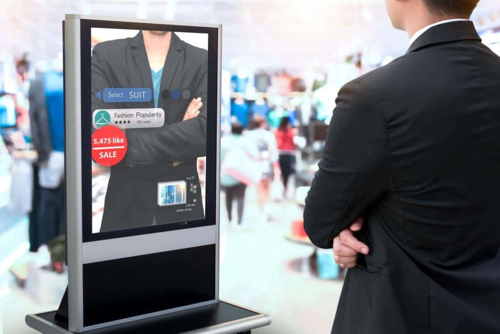 Man stands in front of digital signage, looking at a picture of another man in a suit with his arms crossed.