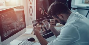 Man slumps over desk looking at negative graphs on a computer, which is why you should be preparing your business for a recession.
