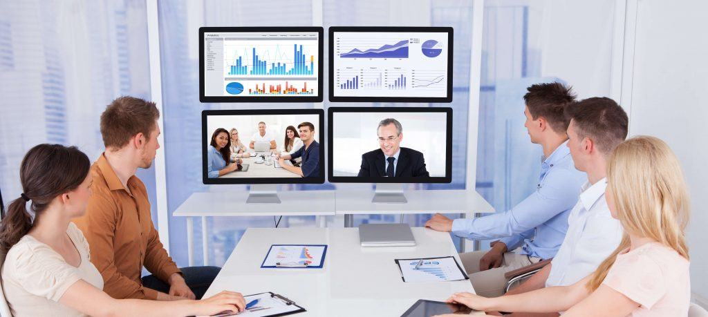 Five employees speak to their manager and coworkers via a web conference, utilizing AVaaS to easily connect. There are also several graphs on screen.