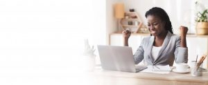 Woman happily sits at computer, glad to have multi-factor authentication.
