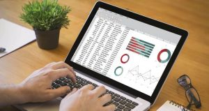 Picture of hands typing on keyboard with a screen showing data analytics tools.