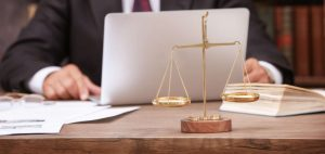 Lawyer types at computer in front of justice scales. He should consider IT legal services for protection.