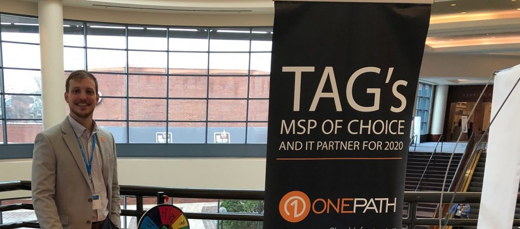 Jon Ulrich smiles behind Onepath booth, happy to be attending the TAG Summit.