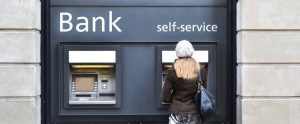Woman stands outside self service at bank, depositing check, thus showing the importance of IT in financial services.