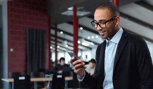 Businessman holds phone in office and smiles--he knows how to avoid smishing attacks.
