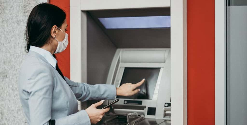 A young lady accesses an ATM while taking precautions due to Coronavirus.