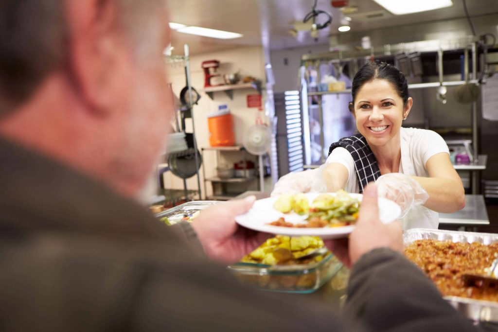 Woman serves man food at SafeHouse Outreach.